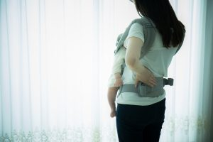 Babywearing mother with backpain